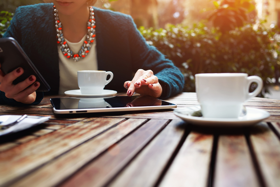 Cup of coffee on the foreground with elegant young woman using busy touch screen tablet at the coffee shop wooden table work break of business people flare sun light